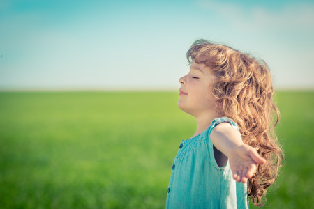 Happy child in spring field relax outdoors Stock Photo
