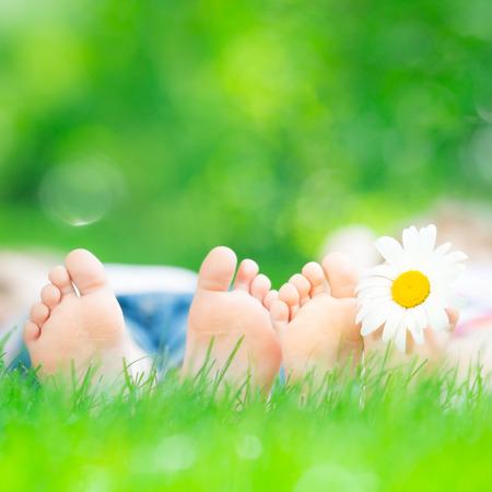 Children lying on green grass