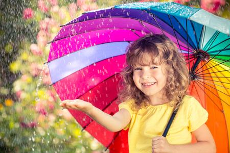 Gelukkig kind in de regen buiten in het voorjaar park Stockfoto