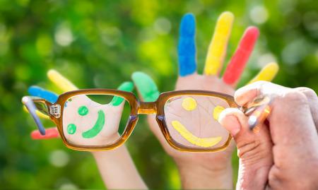 Gafas en la mano, sonriente en las manos contra el fondo verde de la primavera
