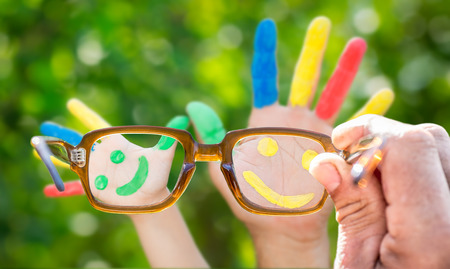 Glasses in hand, Smiley on hands against green spring background