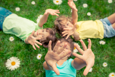 spring season: Happy children lying on grass. Funny kids playing in park. Beautiful spring flowers Stock Photo