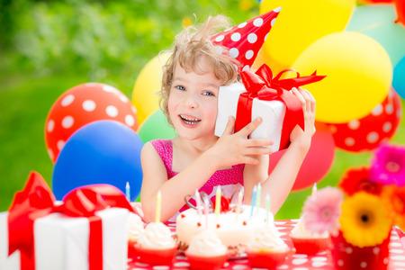 balloons green: Happy child celebrating birthday having fun in spring garden Stock Photo