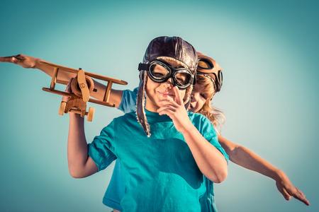 Felices los niños jugando con avión de cosecha de madera al aire libre. Retrato de los niños contra el fondo del cielo de verano. Viajes y concepto de la libertad. Retro tonificado