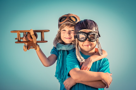 Happy kids playing with vintage wooden airplane outdoors. Portrait of children against summer sky background. Travel and freedom concept. Retro toned photo