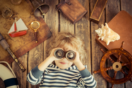 幸せな子供の海事の物で遊ぶこと。子供は、自宅で楽しんで。旅行や冒険の概念。珍しい高角度表示肖像画