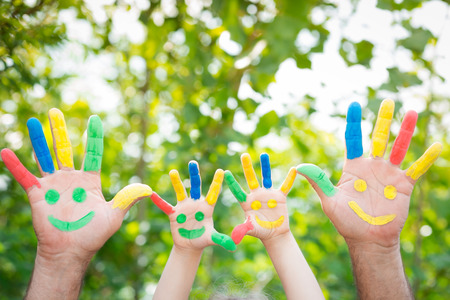 smiley: Smiley on hands against green spring background. Family having fun outdoors