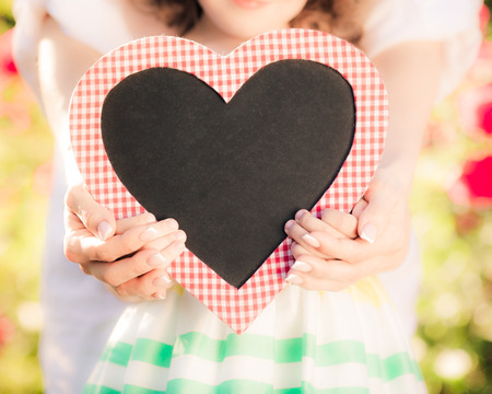 mother: Happy woman and child holding heart shape blackboard blank against spring background. Family holiday concept. Mothers day