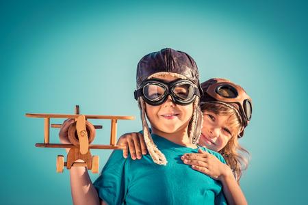 Gelukkig kinderen spelen met vintage houten vliegtuig buiten. Portret van kinderen tegen de zomer hemel achtergrond. Reizen en vrijheid concept. Retro afgezwakt Stockfoto