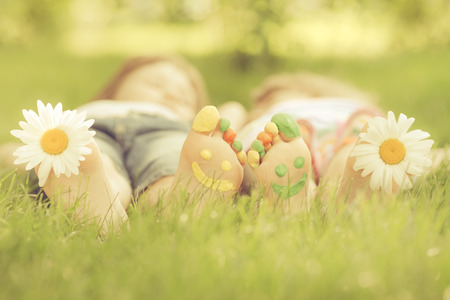 Family lying on green grass. Children having fun outdoors in spring park. Retro toned image