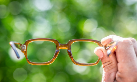 Glasses in hand. Blurred green spring background