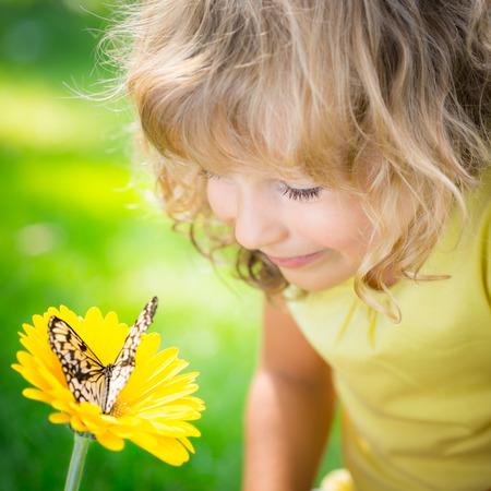 Niño hermoso con la mariposa en el parque de la primavera. Cabrito feliz que juega al aire libre