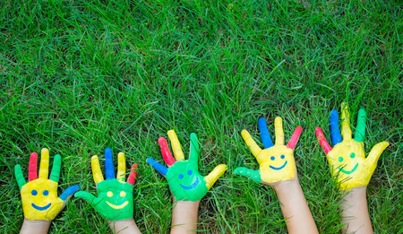 Group of happy people on green grass. Family having fun in spring. Smiley on hands. Ecology concept. Top view portrait