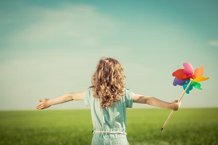 felicidad: Niño feliz en el campo de primavera. Chica joven se relaja al aire libre. Concepto de la libertad