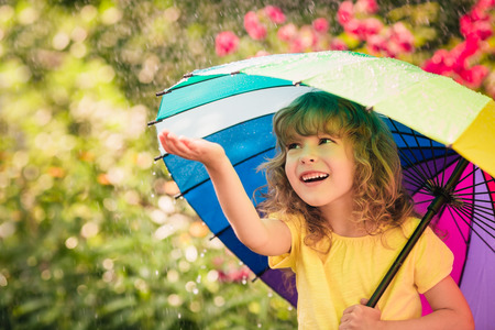 rainbow umbrella: Happy child in the rain. Funny kid playing outdoors in spring park