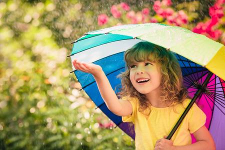 � spring: Ni�o feliz en la lluvia. Cabrito divertido jugando al aire libre en el parque de la primavera
