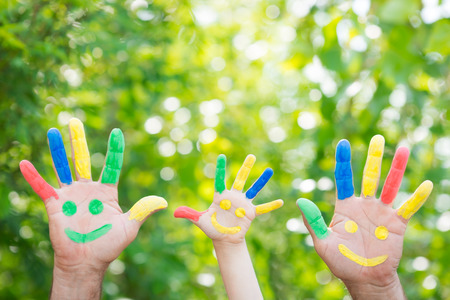 Smiley on hands against green spring background. Family having fun outdoors
