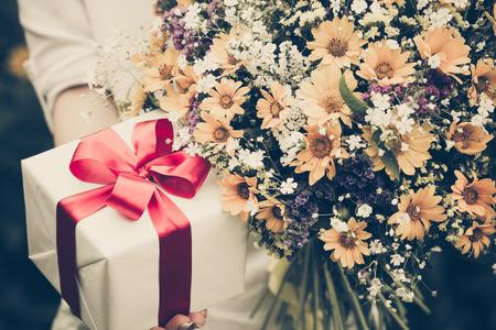 Geschenk-Box und Blumen in den Händen gegen den Frühling Hintergrund. Familienurlaub Konzept. Muttertag Standard-Bild
