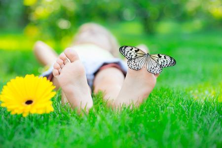 jolie pieds: Enfants pieds dans l'herbe verte. Papillon sur une fleur de printemps