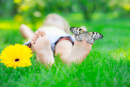 Kinderfüße im grünen Gras. Schmetterling auf Frühlingsblume Standard-Bild