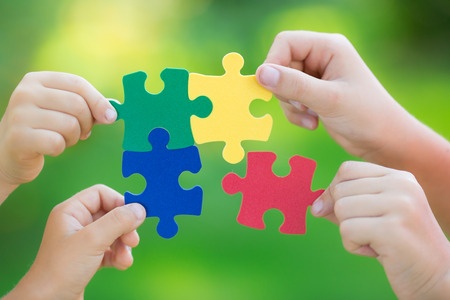 Multicolor puzzles in hands against green spring blurred background. Teamwork and solution concept
