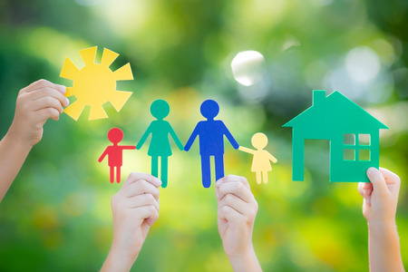 primavera: Casa de papel y la familia en la mano contra el muelle de fondo verde. Inmobiliaria concepto de negocio