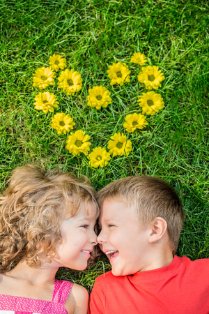 flowers boy: Happy children having fun outdoors. Heart shape spring flowers. Boy and girl lying on green grass. Holiday concept. Valentines day Stock Photo