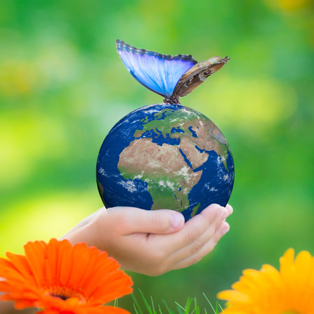 Child holding Earth planet with blue butterfly in hands against green spring background.