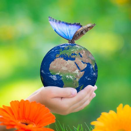 Kind houden planeet Aarde met blauwe vlinder in handen tegen groene lente achtergrond.