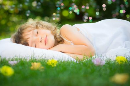 Happy kid sleeping on green grass outdoors in spring garden photo