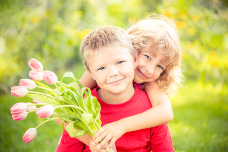 first love: Happy children with bouquet of flowers. Boy and girl against green background. Spring family holiday concept. Womens day Stock Photo