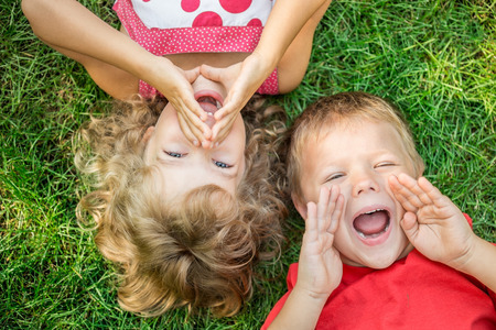 Grappige kinderen geschreeuw buiten. Gelukkige kinderen liggen op groen gras. Communicatie concept Stockfoto