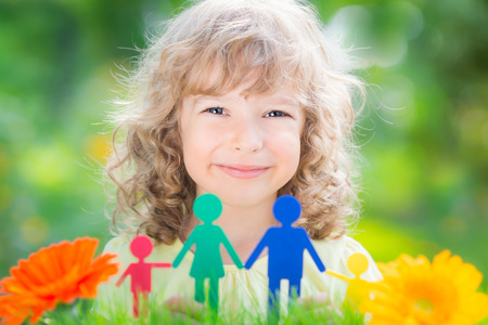 Happy child holding paper family in hands against spring green background photo