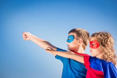 Niños Superhero contra fondo del cielo de verano. Niños que se divierten al aire libre. Niño y niña jugando. El éxito y el concepto del ganador