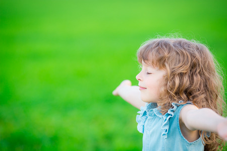 Happy child relaxing outdoors in spring filed Stock Photo