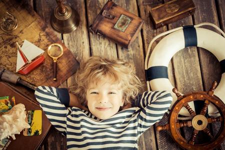 reizen: Gelukkige jongen speelt met nautische dingen. Kind plezier thuis. Reizen en avontuur concept. Ongewoon hoge hoek mening portret