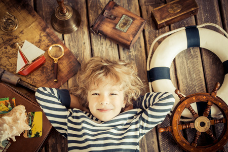 unusual angle: Happy kid playing with nautical things. Child having fun at home. Travel and adventure concept. Unusual high angle view portrait Stock Photo