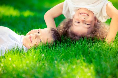 Bambini felici in piedi a testa in giù sull'erba verde. Bambini sorridenti divertirsi nel parco di primavera. Concetto di stile di vita sano