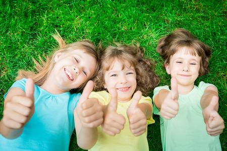 Счастливые дети, лежащие на зеленой траве в парке весной. Смеясь дети показывает палец вверх