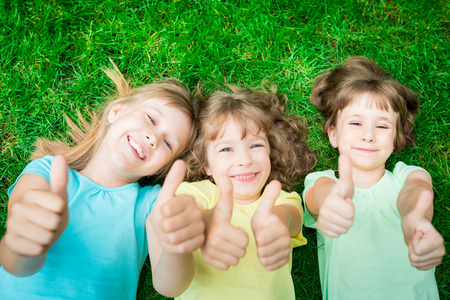 children face: Happy children lying on green grass in spring park. Laughing kids showing thumbs up