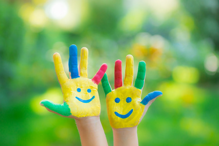 green smiley face: Smiley hands against green blurred background. Children having fun in spring outdoors. Ecology concept Stock Photo