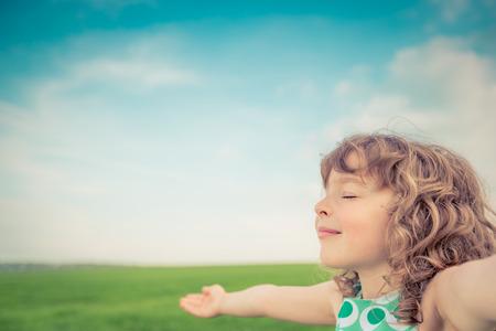 スプリング フィールドで幸せな子供。若い女の子は屋外にリラックスします。自由の概念