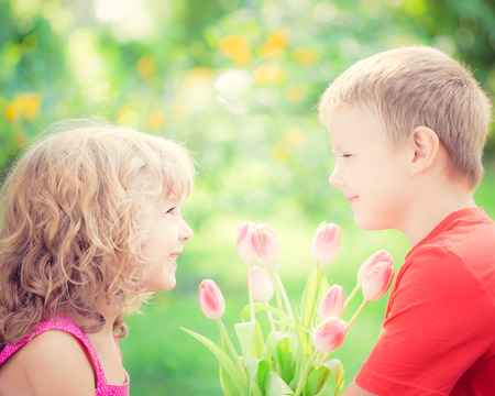 first day: Happy children with bouquet of flowers. Boy and girl against green background. Spring family holiday concept. Womens day Stock Photo