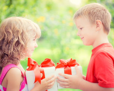 flowers boy: Happy children with bouquet of flowers. Boy and girl against green background. Spring family holiday concept. Womens day Stock Photo