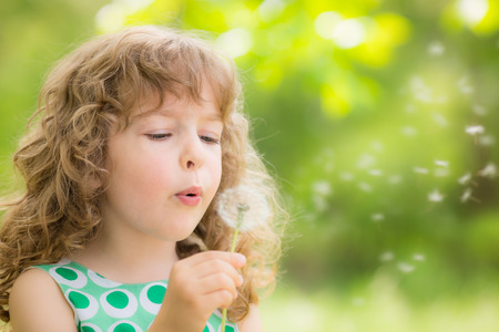 sick child: Beautiful child with dandelion flower in spring park. Happy kid having fun outdoors
