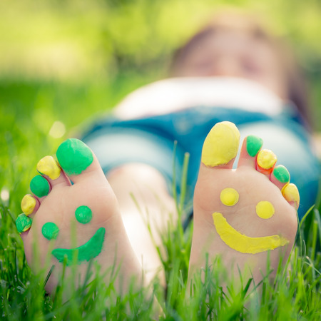 smiley: Child lying on green grass. Kid having fun outdoors in spring park