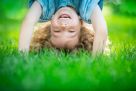 upside down: Happy child standing upside down on green grass. Laughing kid having fun in spring park. Healthy lifestyle concept