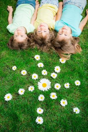 Grupo de niños felices jugando al aire libre en la primavera de parque Foto de archivo