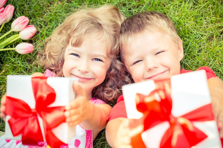 flowers boy: Happy children with bouquet of flowers. Boy and girl against green background. Spring family holiday concept. Womens day. Unusual top view portrait Stock Photo