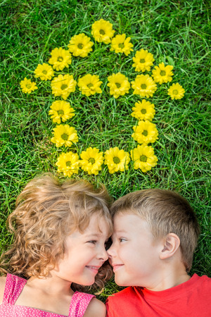 flowers boy: Happy children having fun outdoors. House shape spring flowers. Boy and girl lying on green grass. Sweet home. Renovation and moving concept
